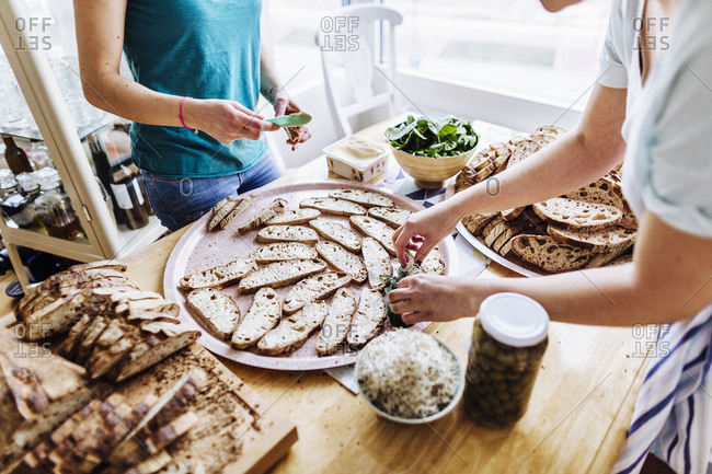Women work together in kitchen to make crostini