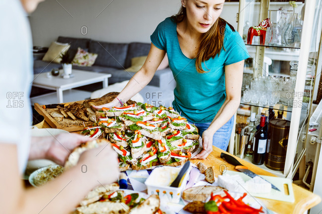 Two women preparing large platter of crostini for party