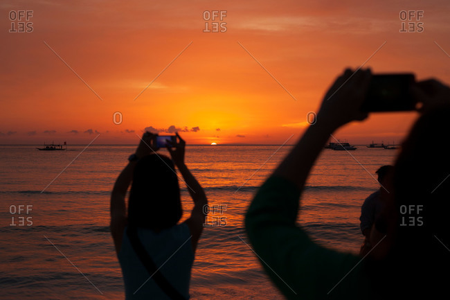 People taking ocean sunset photos, Boracay, Philippines