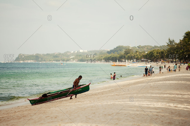 Borocay, Philippines - February 19, 2013: Man pulling boat onto beach, Borocay, Philippines