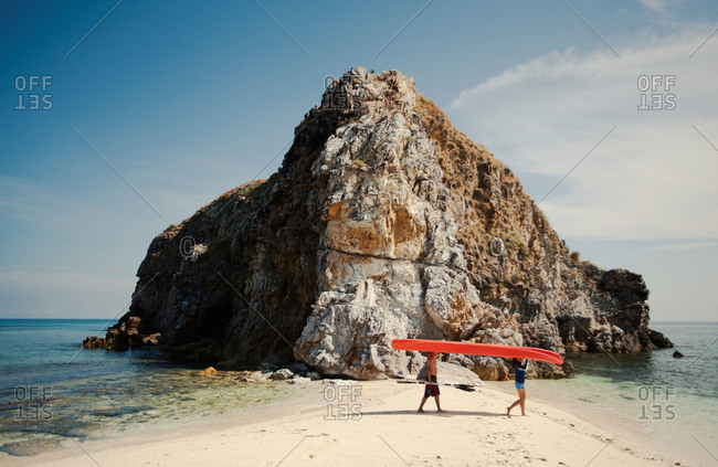 Kayakers carrying boat past rock formation, Philippines