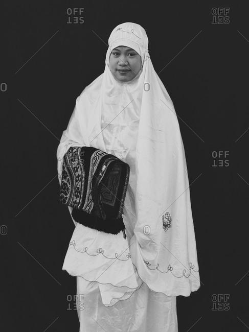 Bukidnon, Philippines - August 7, 2013: Muslim women holding prayer rug, Philippines