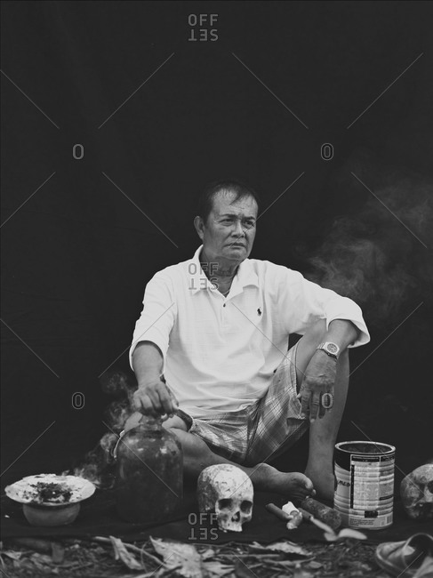 Siquijor, Philippines - September 11, 2013: Faith healer sitting with skulls, Philippines