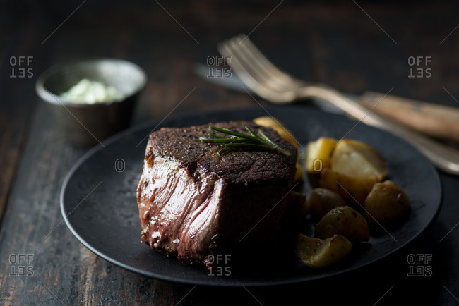 Filet mignon with spring of rosemary on a black plate with potatoes