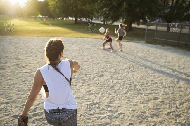 Woman throwing ball to teammate during baseball game