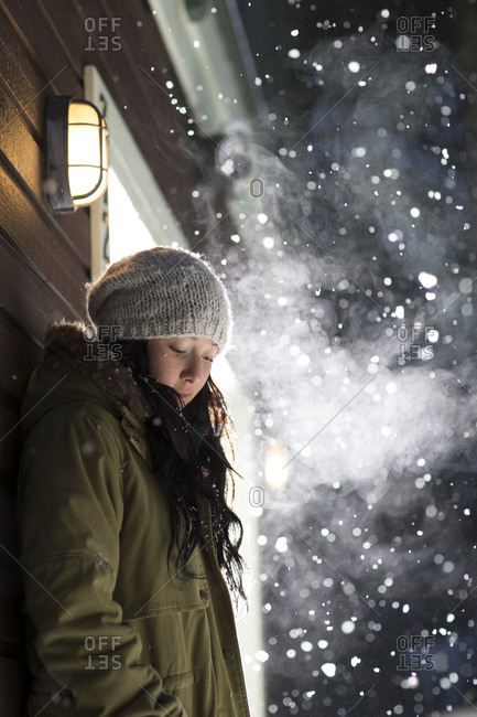 Woman standing out in the cold at night