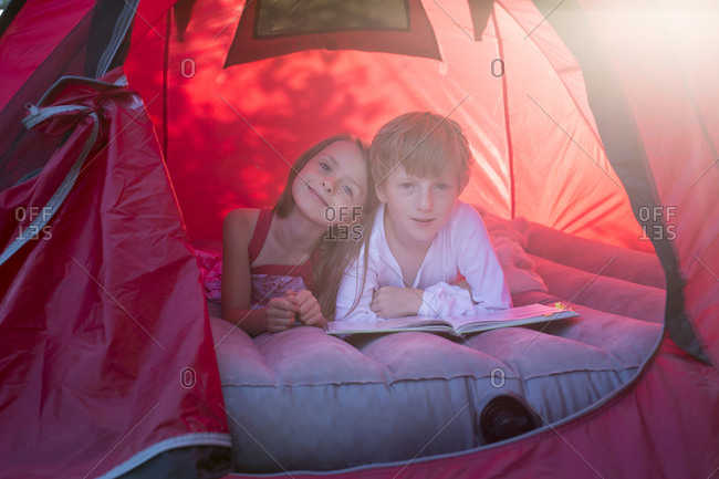 Portrait of brother and sister lying in a red tent with a book