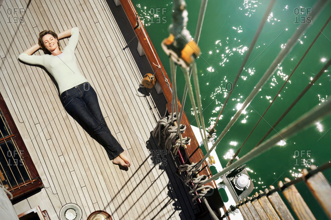 Relaxed mature woman lying on deck of a sailing ship