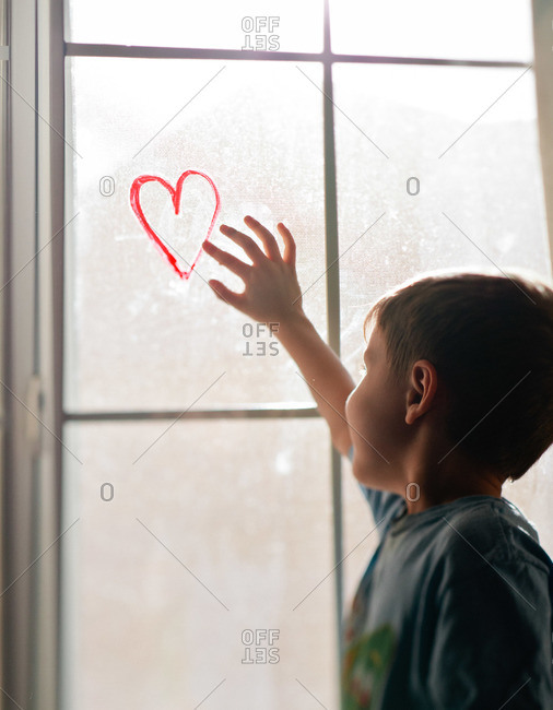 A young boy reaches up to a heart drawn on a window
