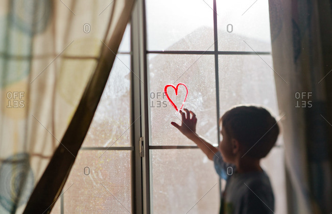 A boy touches a window with a heart drawn on it