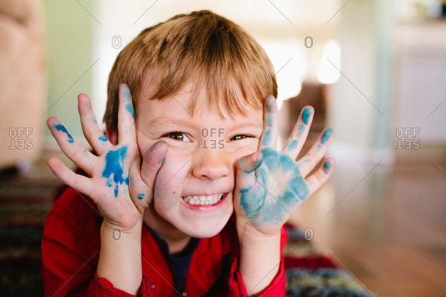 A boy with blue marker on his hands