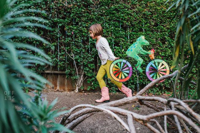 A girl drags a yard sculpture through her yard