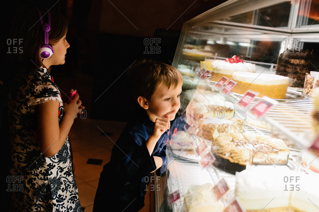 A boy points to a cake he wants in a display case