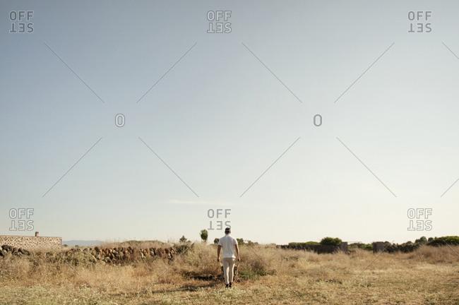 Man pushing a wheelbarrow in a field