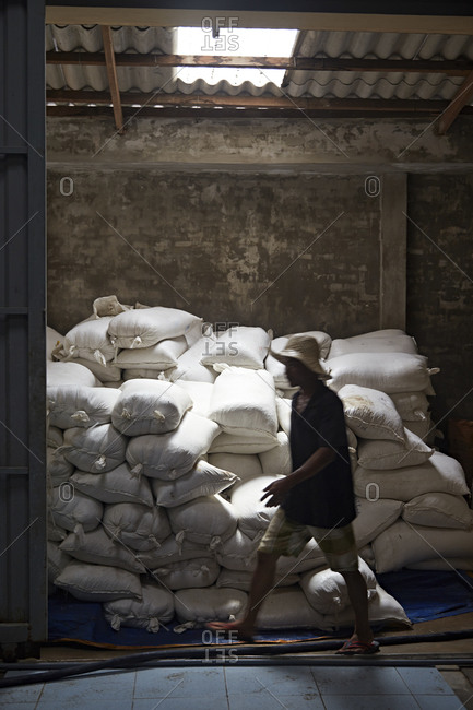 Man walks past sacks of ingredients in a fish sauce factory in Vietnam