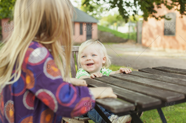 Toddler laughing with girl at park table