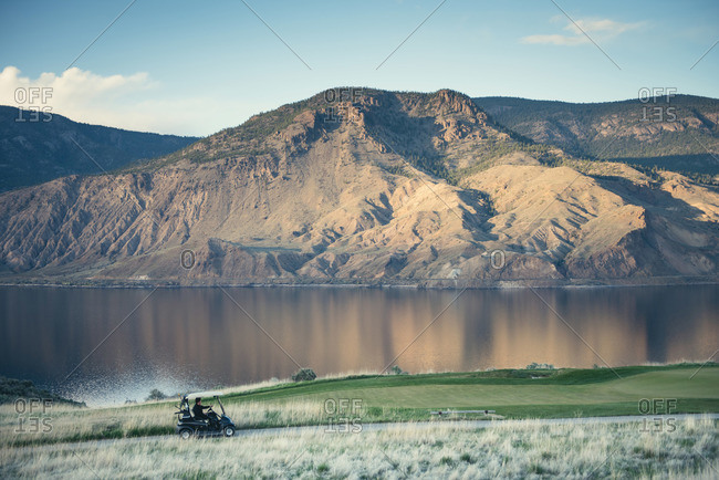 A man drives a golf cart by a lake in Kamloops, Canada