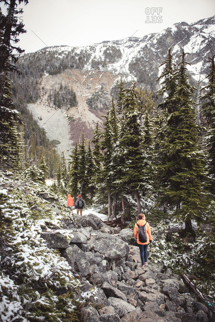 Three hikers walk on a rocky path in Joffre Lakes Provincial Park, Canada