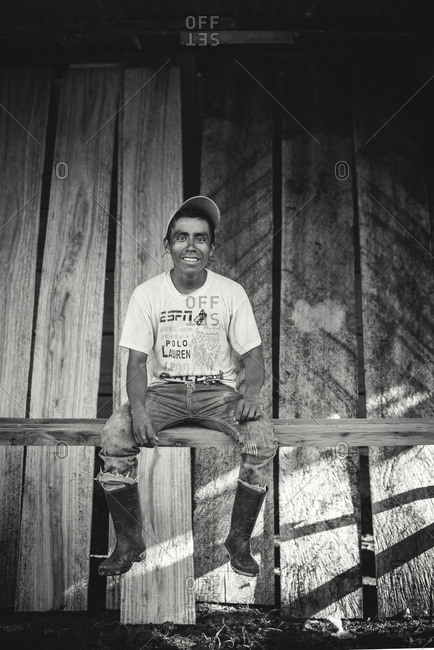 Guatemala - May 5, 2015: A Guatemalan man sits on a wood beam