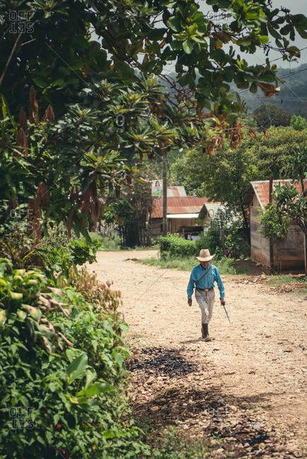 Guatemala - May 14, 2015: An old man walks up a dirt road in a village in Guatemala