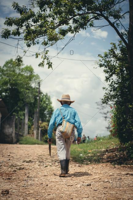An old man with a machete walks up a dirt road