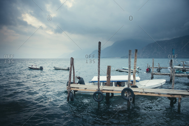 Fishermen docking their boats before a storm at Lago Atitlan, Guatemala