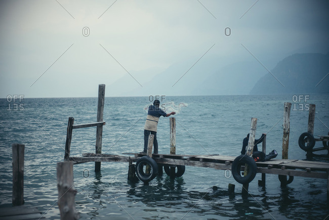 A fisherman casts out a net from a dock at Lago Atitlan, Guatemala