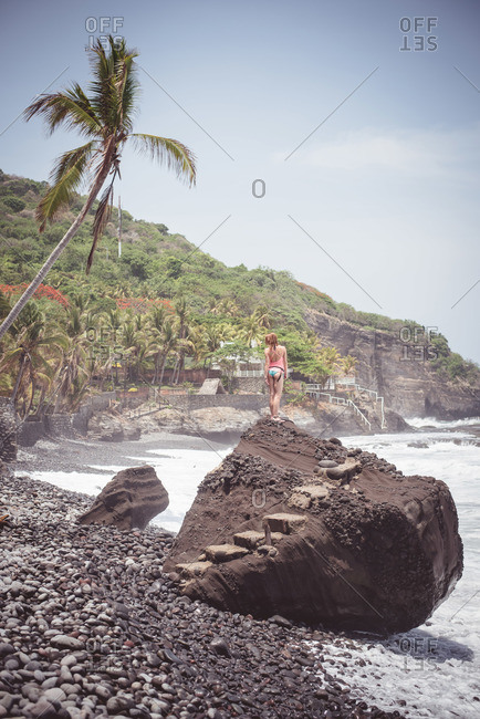 A woman stands on a rock at El Zonte, El Salvador