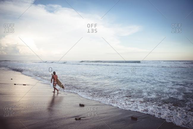 A surfer walks along beach in Nicaragua