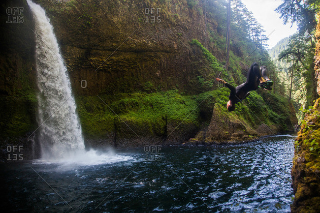 A man does a backflip into the water at Eagle Creek Falls in Columbia Gorge, Oregon