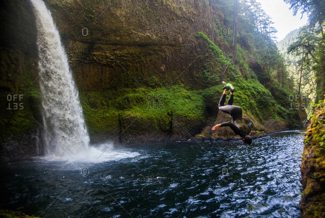 A man does a backflip at a swimming hole at Eagle Creek Falls in Columbia Gorge, Oregon