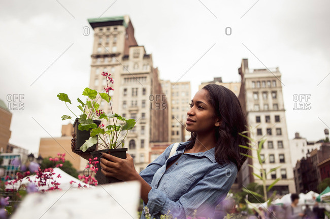 A woman looks at a flowering plant at a farmer's market