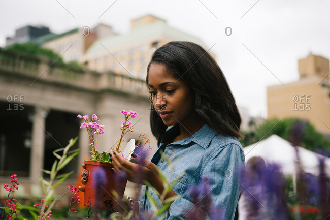 A woman looks at a potted plant at an outdoor farmer's market