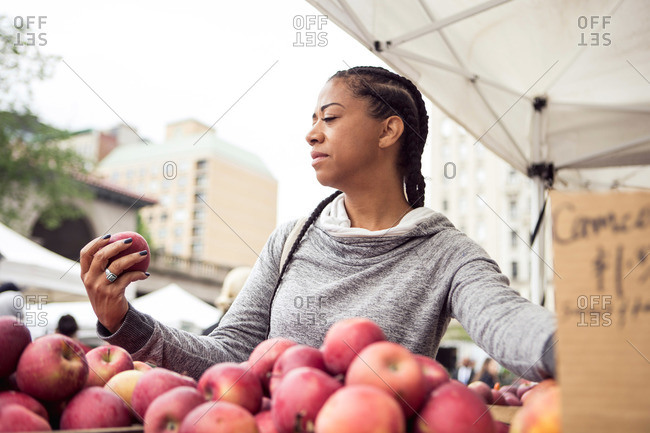 A woman looks at an apple at a farmer's market
