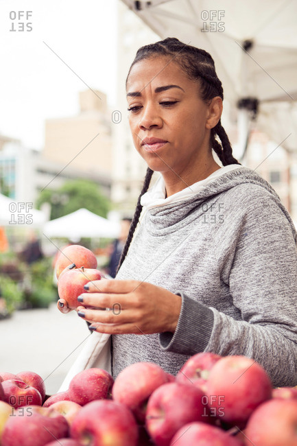 A woman evaluates apples at a farmer's market