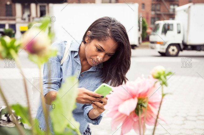 A woman checks her phone while shopping for flowers