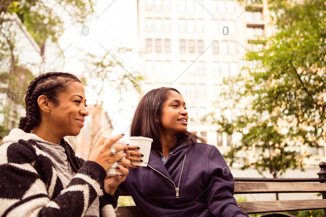 Two women with coffee cups on a park bench