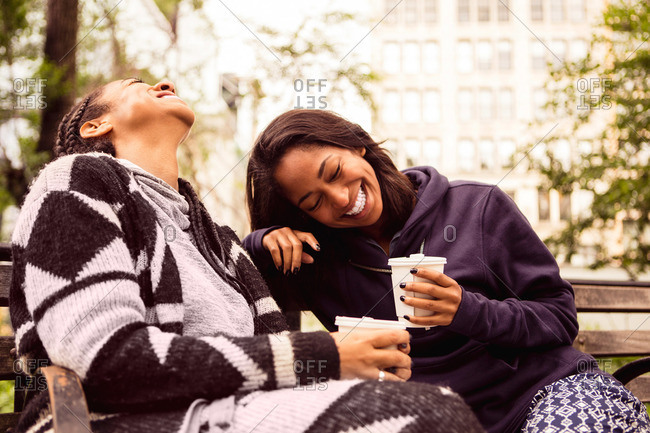 Two women laugh together while drinking coffee on a park bench