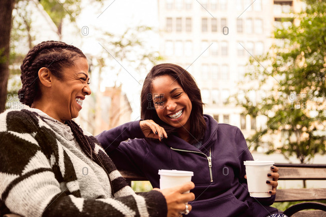 Two women laughing together while drinking coffee on a park bench