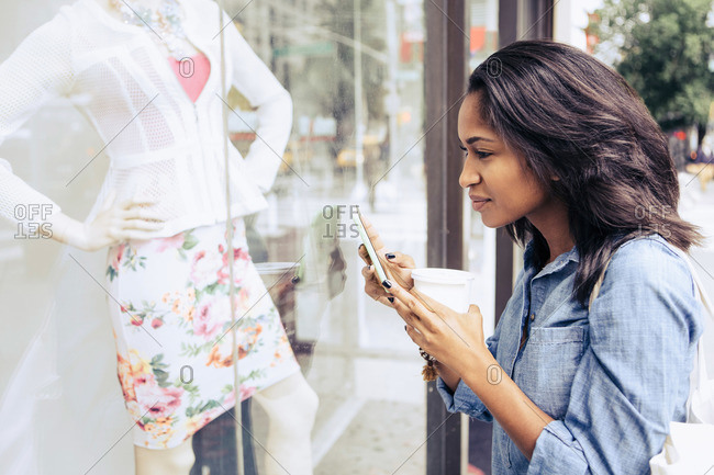 A woman uses her phone in front of a window display