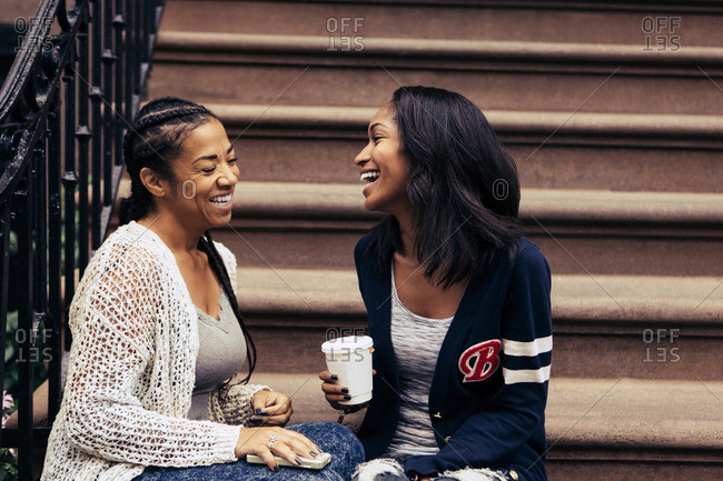 Two women laugh while chatting on a stoop