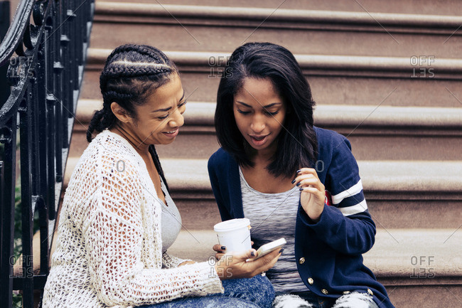 A woman shows her friend something on her phone