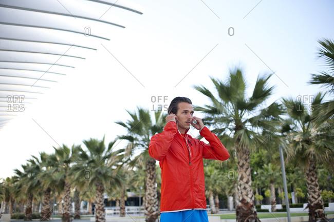 A jogger adjusts his earbuds