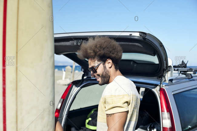 A man smile while unloading surfing gear from his car
