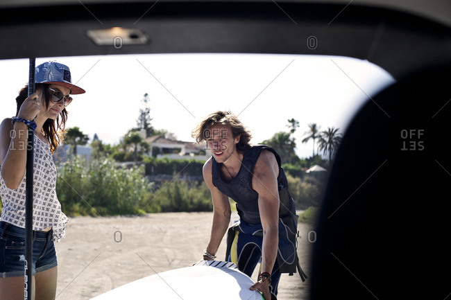 A surfer takes a surfboard out of a car