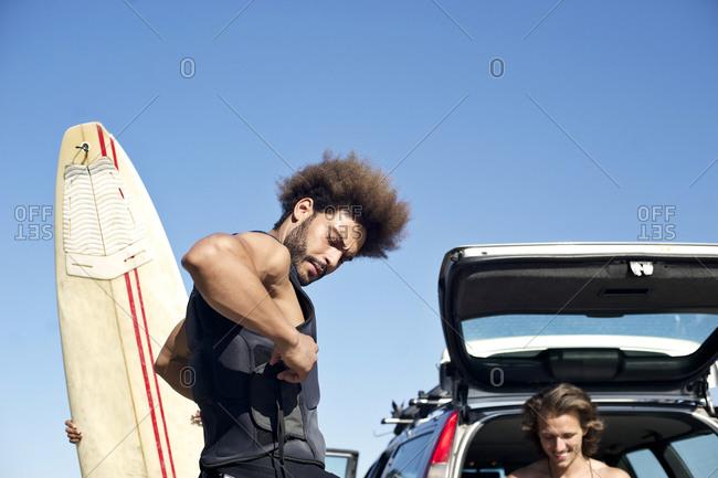 A surfer puts on a wetsuit vest
