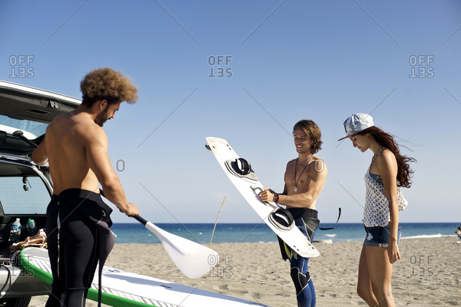Friends prepare to surf and paddle board