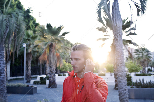 A jogger adjusts his earbuds in a park