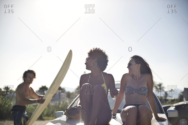 Two women hang out on the hood of a car at the beach