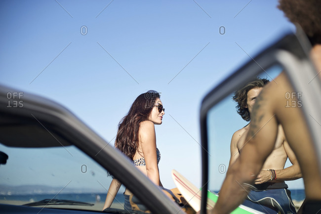 Friends hang out by a car on the beach